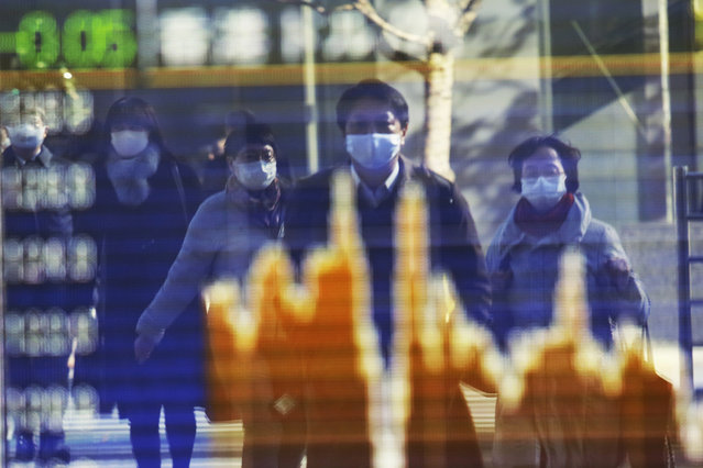 People wearing face masks to protect against the spread of the coronavirus reflected on the electronic board of a securities firm in Tokyo, Wednesday, Dec.16, 2020. Asian shares are higher Thursday, December 17, 2020 on hopes the U.S. Congress may finally deliver fresh aid to help businesses and families weather the pandemic. (Photo by Koji Sasahara/AP Photo)