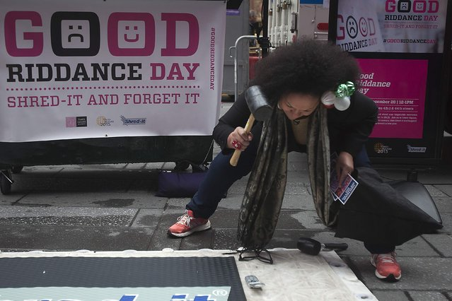 "Actress Boquita Almonte smashes an old cell phone on ""Good Riddance Day"" in Times Square in New York December 28, 2014. Good Riddance Day, inspired by Latin American tradition, encourages people to shred and smash their bad memories from 2014 to start the new year fresh. (Photo by Carlo Allegri/Reuters)"