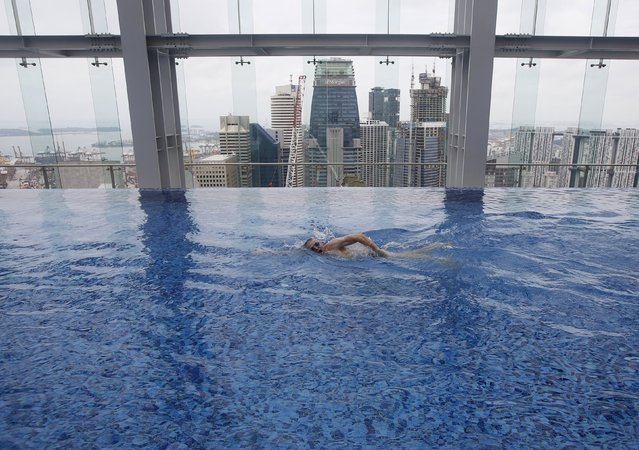 A man swims in a rooftop indoor swimming pool in the central business district in Singapore July 15, 2015. (Photo by Edgar Su/Reuters)