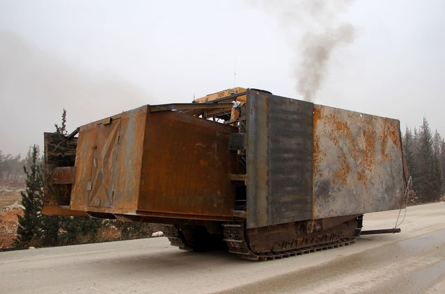 Rebel fighters from the Jaish al- Fatah (or Army of Conquest) brigades manoeuver an alleged explosive- rigged make- shift armoured vehicle during a major assault on Syrian government forces West of Aleppo city on October 28, 2016 Syrian opposition fighters launched a major assault on government forces to break a months- long siege of rebel- held neighbourhoods of the battered city of Aleppo. Rebel groups including the powerful Ahrar al- Sham faction and former Al- Qaeda affiliate Fateh al- Sham Front fired waves of rockets into government- held western Aleppo, killing at least 15 civilians, a monitor said. (Photo by Omar Haj Kadour/AFP Photo)