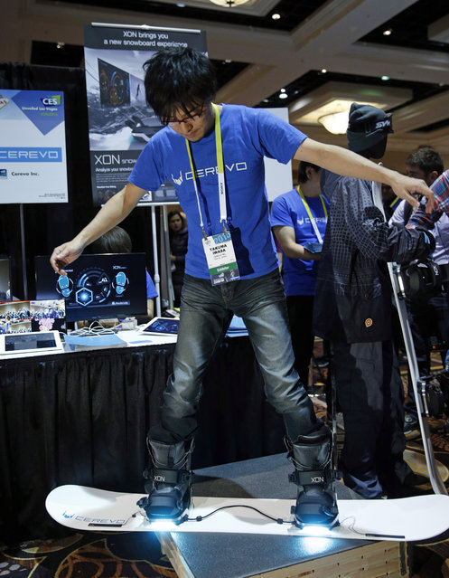 Takuma Iwasa demonstrates the Cerevo XON Snow-1 snowboard bindings at CES Unveiled, a media preview event for CES International, Sunday, January 4, 2015, in Las Vegas. The bindings have pressure sensors to analyze your snowboarding technique. (Photo by John Locher/AP Photo)