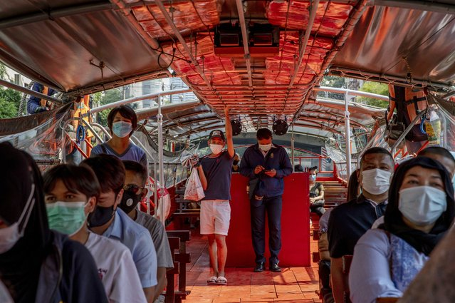 Passengers wearing face-masks to reduce the spread of the coronavirus, ride a canal ferry in Bangkok, Thailand, Wednesday, January 6, 2021. Thailand planned to expand testing to thousands of factories in a province next to Bangkok as it reported over 300 new virus cases around the country on Wednesday and one new death, an official said. (Photo by Gemunu Amarasinghe/AP Photo)