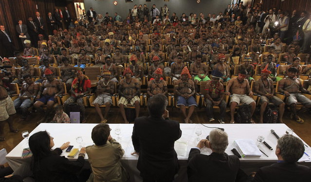 Minister of the General Secretariat of the Presidency of Brazil, Gilberto Carvalho (C), speaks to Munduruku Indians during a meeting at the Planalto Palace in Brasilia, June 4, 2013. President Dilma Rousseff's government sought on Tuesday to defuse mounting conflicts with indigenous groups over its decision to stop setting aside farm land for Indians and plans to build more hydroelectric dams in the Amazon. The government flew 144 Munduruku Indians to Brasilia for talks to end a week-long occupation of the controversial Belo Monte dam on the Xingu river, a huge project aimed at feeding Brazil's fast-growing demand for electricity. (Photo by Ueslei Marcelino/Reuters)