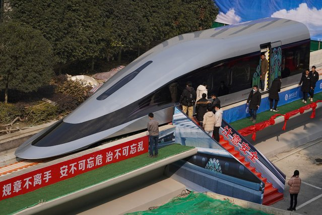 People visit a prototype magnetic levitation train developed with high-temperature superconducting (HTS) maglev technology at the launch ceremony in Chengdu, in southwestern China's Sichuan province on January 13, 2021. It's designed to travel at 385 miles per hour. (Photo by AFP Photo/China Stringer Network)