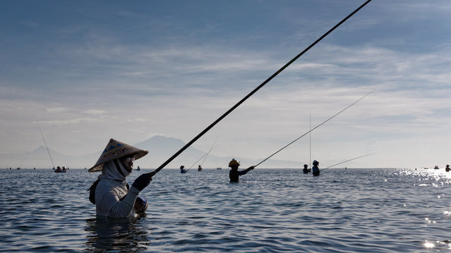 """""""Waking up with the fishermen"""". It's just past 8am and most are already in for a while. As the sun rises and reveals Bali's Gunung Agung volcano in the far distance, more and more men gather in the sea and paint the horizon with their silhouettes as far as the eye can see. They fish for very small fish and will stand here for many hours, until well beyond noon, to fill the bags they carry on their hips. Many of them wear life jackets because they cannot swim. Their hats come in all sorts and shapes and double as toolkits, with pouches glued to the inside or outside to keep their gear and cigarettes within easy reach. Location: Sanur, Bali, Indonesia. (Photo and caption by Willem Sorm/National Geographic Traveler Photo Contest)"""