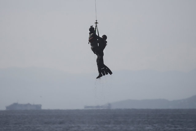 A Greek paratrooper (R) is rescued during a mock Search and Rescue operation, during a show marking the Hellenic Air Force's Patron Saint celebration, on the southern suburb of Faliro, in Athens, Greece, November 6, 2016. (Photo by Alkis Konstantinidis/Reuters)