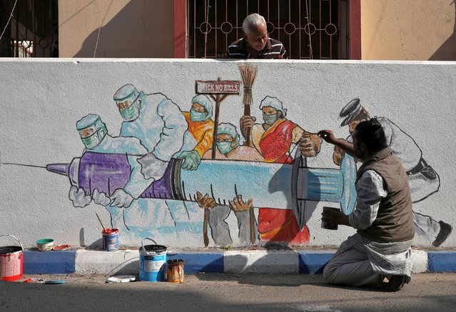 A man applies finishing touches to graffiti representing a vaccine, amidst the spread of coronavirus disease (COVID-19) in Kolkata, India, January 2, 2021. (Photo by Rupak De Chowdhuri/Reuters)