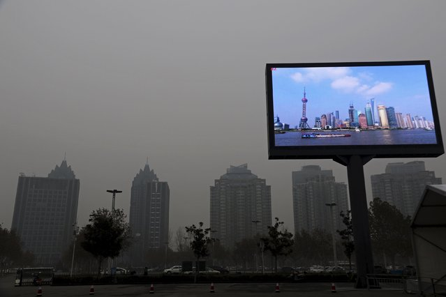 A electric screen showing Shanghai Pudong financial area in a clear day is seen amid heavy smog in Zhengzhou, Henan province, China, December 9, 2015. (Photo by Reuters/Stringer)