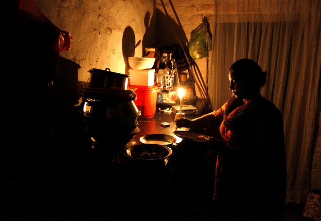 A woman cleans up after dinner in her home during a power cut in Islamabad, Pakistan October 8,  2016. Picture taken October 8, 201. (Photo by Caren Firouz/Reuters)