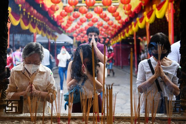 People pray at a temple ahead of the Lunar New Year celebration in Bangkok, Thailand, February 10, 2021. (Photo by Chalinee Thirasupa/Reuters)