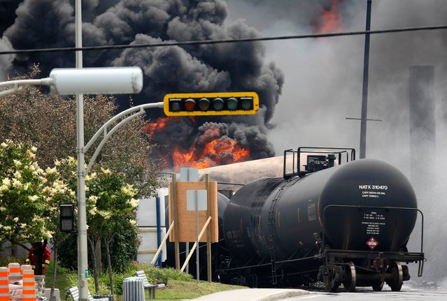 A burning train wagon is seen after an explosion at Lac Megantic, Quebec, July 6, 2013. (Photo by Mathieu Belanger/Reuters)