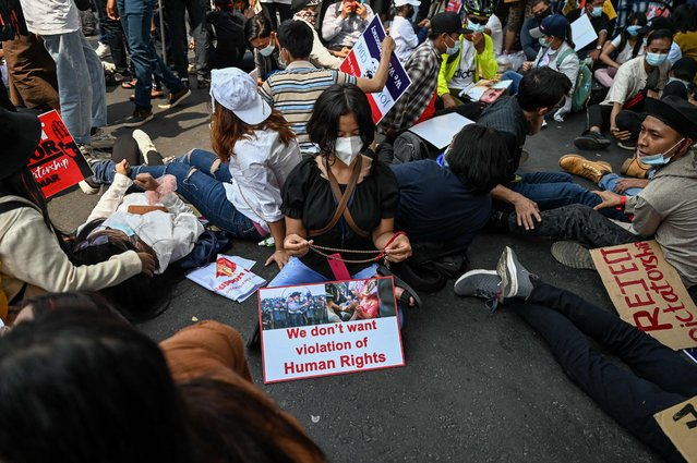Protesters lay down to block a road during a demonstration against the military coup in Yangon on February 20, 2021. (Photo by AFP Photo/Stringer)