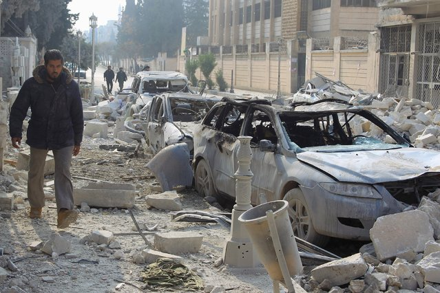 A man walks past damaged cars at a site hit by what activists said were airstrikes carried out by the Russian air force in Idlib city, Syria December 20, 2015. (Photo by Ammar Abdullah/Reuters)