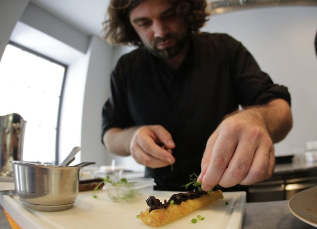 Austrian chef Konstantin Filippou prepares a snail dish in his gourmet restaurant in Vienna July 12, 2013. Andreas Gugumuck owns Vienna's largest snail farm, exporting snails, snail-caviar and snail-liver all over the world. The gourmet snails are processed using old traditional cooking techniques and some are sold locally to Austrian gourmet restaurants. (Photo by Leonhard Foeger/Reuters)