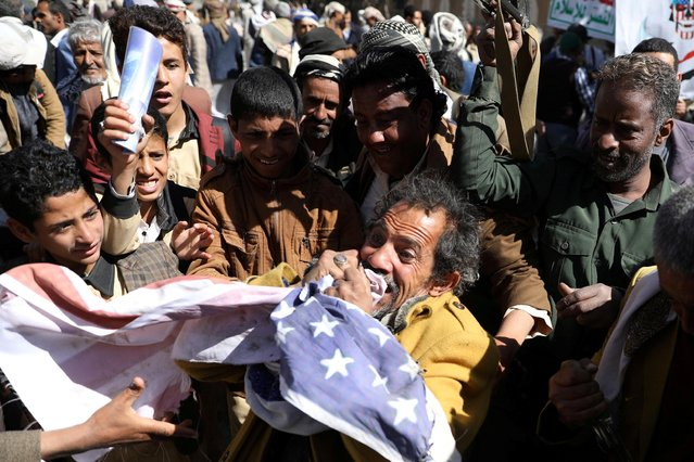 A Houthi supporter reacts as he shatters the U.S. flag during a demonstration outside the U.S. embassy against the United States over its decision to designate the Houthis a foreign terrorist organisation, in Sanaa, Yemen on January 18, 2021. (Photo by Khaled Abdullah/Reuters)