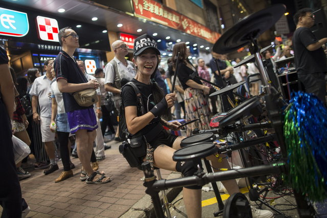 A busker playing drums in Sai Yeung Choi Street South in Mongkok district, Hong Kong, China, 28 July 2018. (Photo by Jerome Favre/EPA/EFE)