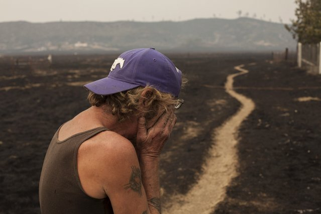 Robert Hooper, exhausted after several days with little sleep, is overcome with emotion while surveying his property that was burnt by the so-called Valley Fire near Middleton, California September 14, 2015. (Photo by David Ryder/Reuters)