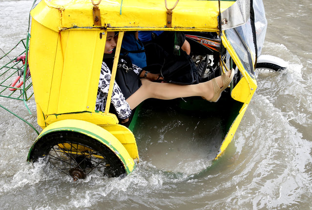 A commuter raises her feet to stay dry as she rides a pedicab, a pedaled tricycle, to go to work amidst flooding in a street in Manila, Philippines, after overnight Southwest monsoon rains brought about by tropical storm Ampil inundated low-lying areas in Metropolitan Manila and nearby provinces Friday, July 20, 2018. (Photo by Bullit Marquez/AP Photo)