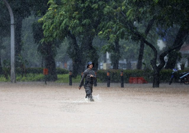A police officer from the mobile brigade walks along a flooded road after heavy seasonal rains flooded parts of Jakarta February 9, 2015. (Photo by Darren Whiteside/Reuters)