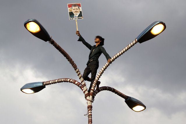 A supporter of deposed Egyptian President Mohamed Mursi climbs up a lamp post during a march in Sanaa, Egypt, on August 16, 2013. (Photo by Mohamed al-Sayaghi/Reuters)