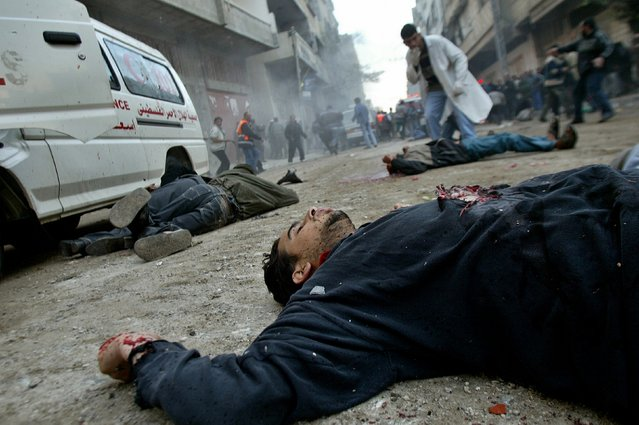 Unidentified bodies lie on a street in the Jabalya refugee camp in northern Gaza Strip, March 6, 2003. Ahmed Jadallah: I was with a Reuters multimedia team to cover incursion a big Israeli incursion to the Gaza Strip. The Israeli tanks had started to withdraw when there was a big fire in one of the buildings due to an air strike. (Photo by Ahmed Jadallah/Reuters)