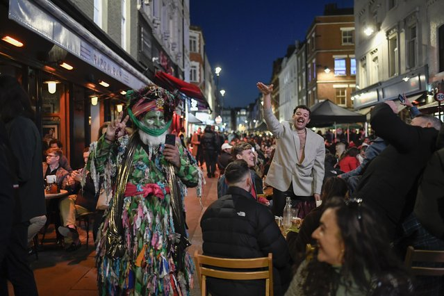 People sit at setup tables outside pubs in Soho, in London, on the day some of England's third coronavirus lockdown restrictions were eased by the British government, Monday, April 12, 2021. Pubs, shops and hairdressers have opened as lockdown restrictions are eased Monday. (Photo by Alberto Pezzali/AP Photo)