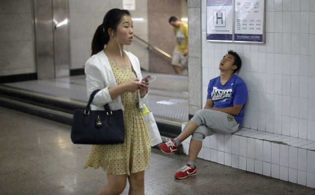 A man sleeps as a woman walks past an entrance to a subway station at an underground passage in central Beijing, June 4, 2013. (Photo by Barry Huang/Reuters)