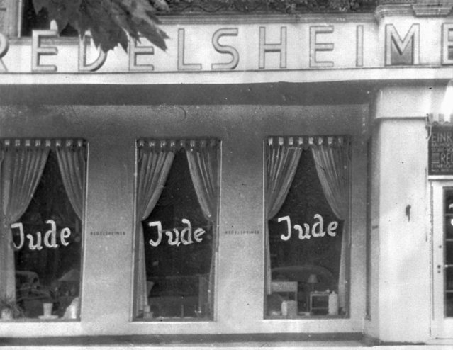 """In this June 19, 1938 file picture, the word Jude (jew) is smeared to the windows of a shop in Berlin run by Jews. On Nov. 9, 1938 Nazi-incited mass riots left more than 91 jews dead, damaged more than 1,000 synagogues and left some 7,500 Jewish businesses ransacked and looted. Before local anti-Jewish laws were enacted, before neighborhood shops and synagogues were destroyed, and before Jews were forced into ghettos, cattle cars, and camps, words were used to stoke the fire of hate. """"ItStartedWithWords"""" is a digital, Holocaust education campaign posting weekly videos of survivors from across the world reflecting on those moments that led up to the Holocaust. (Photo by AP Photo/File)"""