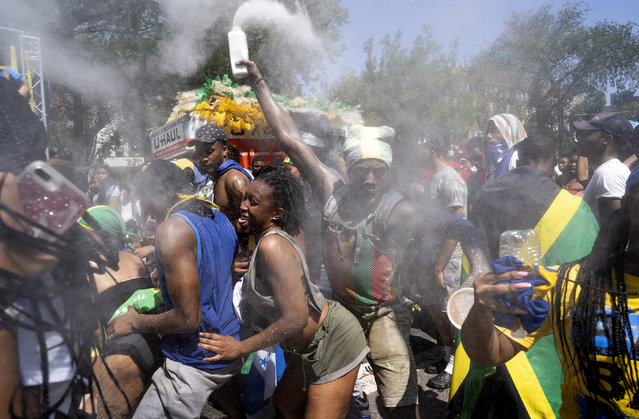 Powder flies in the air over revelers and participants at the the West Indian American Day Parade in the Brooklyn borough of New York, Monday, September 3, 2018. New York's Caribbean community has held annual Carnival celebrations since the 1920s, first in Harlem and then in Brooklyn, where festivities happen on Labor Day. (Photo by Craig Ruttle/AP Photo)