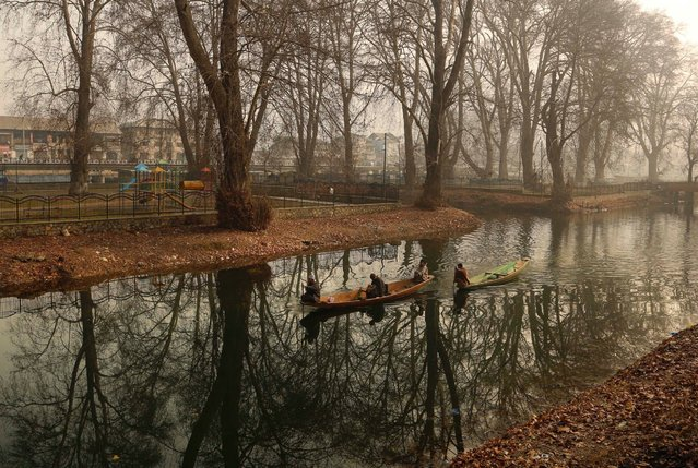 Kashmiri fishermen row their boats on the way to work on a cold morning in Srinagar, Indian controlled Kashmir, December 30, 2015. (Photo by Mukhtar Khan/AP Photo)