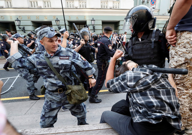 A serviceman of the Russian National Guard beats a protester during a rally against planned increases to the nationwide pension age in Moscow, Russia September 9, 2018. (Photo by Sergei Karpukhin/Reuters)