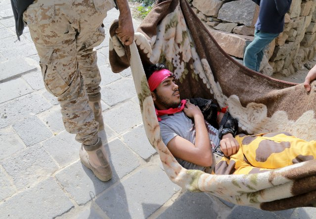 A fighter of the pro-government Popular Resistance Committees, is being carried on a blanket after he was injured during clashes with Houthi fighters in Yemen's southwestern city of Taiz, January 5, 2016. (Photo by Reuters/Stringer)