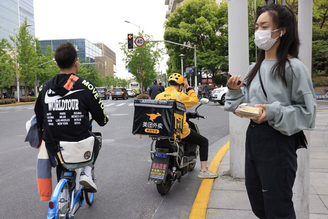 A Meituan delivery man in yellow goes on his rounds in Shanghai on Wednesday, April 21, 2021. China's market regulator on Monday, April 26, 2021 said it launched an investigation into suspected monopolistic behavior by food delivery firm Meituan, months after it investigated e-commerce company Alibaba as Beijing steps up scrutiny of anti-competitive behavior in the internet sector. (Photo by Ng Han Guan/AP Photo)