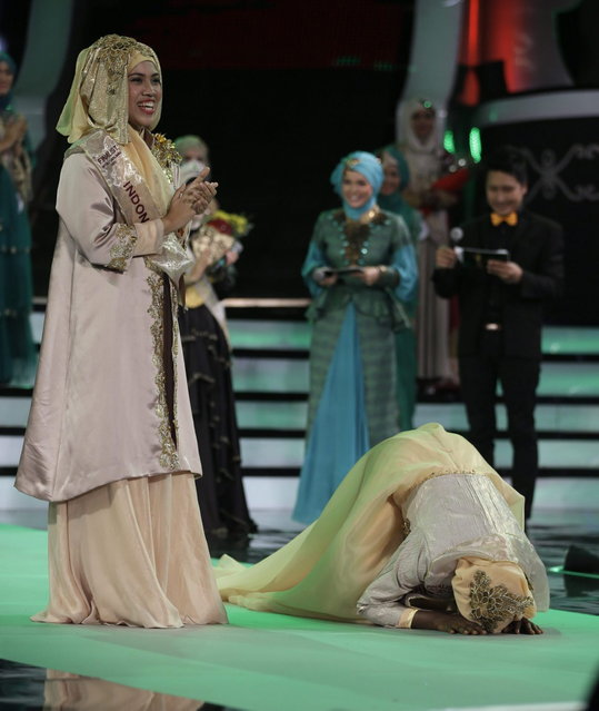Obabiyi Aishah Ajibola, right, kisses the floor after being named World Muslimah 2013, as runner up Noor Aspasia of Indonesia, left, applauds, during the third Annual Award of World Muslimah in Jakarta, Indonesia, Wednesday, September 18, 2013. The annual pageant, held exclusively for Muslim women, assessed not only contestants' appearance but also their piety and religious knowledge. (Photo by Dita Alangkara/AP Photo)
