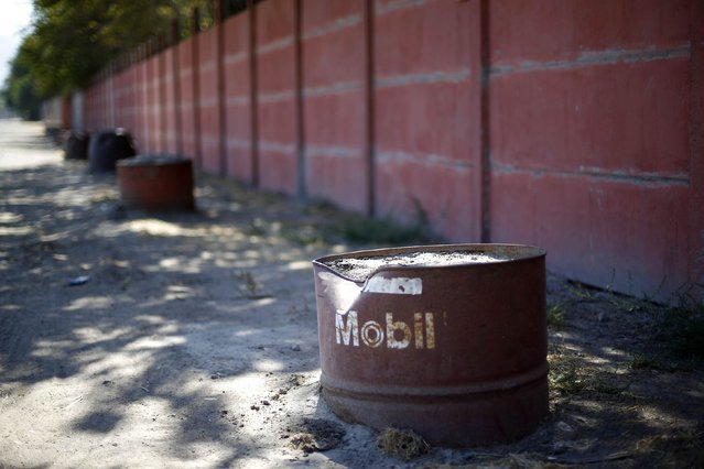 Discarded oil barrels seen being used to protect a wall in a rural area nearby Santiago city, February 16, 2015. (Photo by Ivan Alvarado/Reuters)