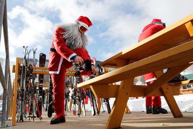 Chuck Ciafardo adjusts his ski boots as he prepares to participate in a Santa-themed charity run down a slope at Sunday River Ski Resort in Newry, Maine December 4, 2016. (Photo by Joel Page/Reuters)