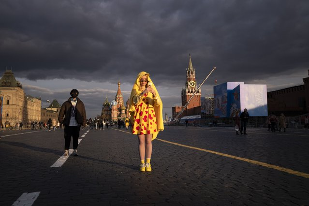 A young woman poses for a selfie at Red Square which is under preparations for the Victory Parade during sunset in Moscow, Russia, Monday, April 26, 2021. Russia will celebrate celebrate 76 years of the victory in WWII on May 9, 2021. (Photo by Alexander Zemlianichenko/AP Photo)