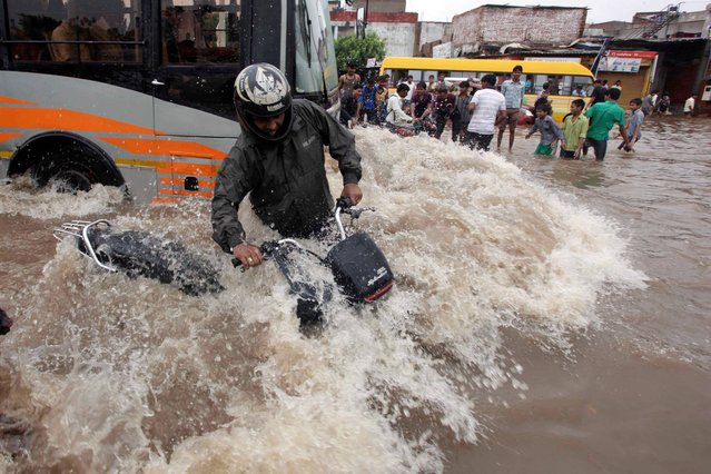 An Indian motorist tries to balance himself as a bus drives past him on a flooded road after heavy rains in Ahmadabad, India, Wednesday, September 25, 2013. Massive flooding has forced 15,000 people to evacuate villages in the west Indian state of Gujarat where heavy rains and swollen rivers have inundated cities and closed off roads and railway lines. (Photo by Ajit Solanki/AP Photo)