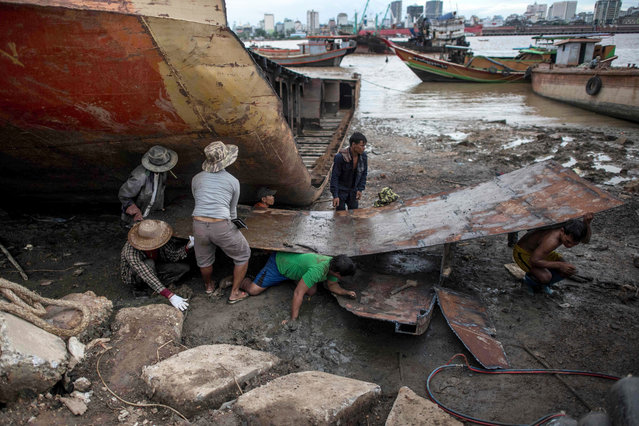 Workers carry a metal sheet dismantled from a ship at a ship-breaking yard on the bank of the Yangon River in Yangon, Myanmar on May 26, 2018. (Photo by Ye Aung/AFP Photo)