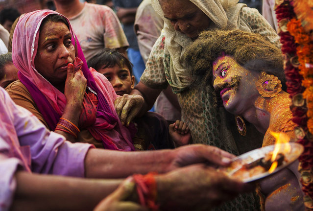 An Indian Hindu devotee looks AT an idol as others perform rituals as part of the Durga Puja festival in New Delhi on October 13, 2013. Durga Puja commemorates the slaying of demon king Mahishasur by goddess Durga, marking the triumph of good over evil. (Photo by Andrew Caballero-Reynolds/AFP Photo)