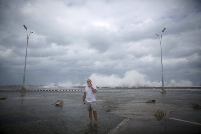 Tim Dixon of the U.S. smokes a cigar next to waves breaking at the seafront Malecon in Havana, January 23, 2016. (Photo by Alexandre Meneghini/Reuters)