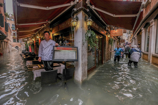 A restaurant owner looks at the flood waters on October 29, 2018 in Venice, Italy. (Photo by Stefano Mazzola/Awakening/Getty Images)