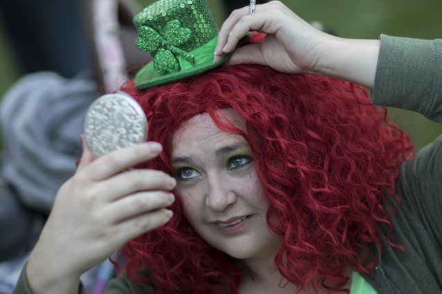Aimee Norton puts the finishing touch on her outfit before the start of the St. Patrick's Day parade, Tuesday, March 17, 2015, in Savannah, Ga. (Photo by Stephen B. Morton/AP Photo)