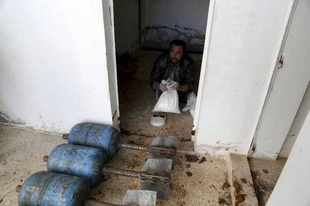 An Islamic Ahrar al-Sham fighter makes shells in preparation to fire them towards forces loyal to Syria's president Bashar Al-Assad on the frontline of Idlib city in northern Syria, where they announced a battle to liberate the city March 21, 2015. (Photo by Khalil Ashawi/Reuters)