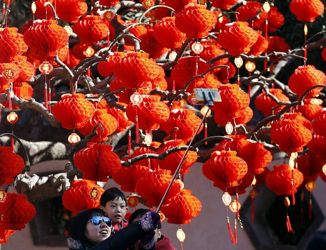 A family uses a selfie stick, in front of a tree decorated with paper lanterns at the Temple Fair, which is part of Chinese New Year celebrations at Ditan Park, also known as the Temple of Earth, in Beijing, February 18, 2015. (Photo by Kim Kyung-Hoon/Reuters)