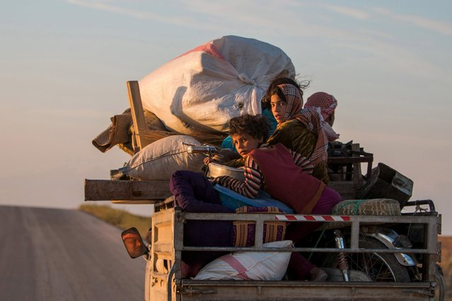 Residents, with their belongings, return to their villages on a pickup truck after Kurdish People's Protection Units (YPG) fighters said that they retook control of the area from Islamic State in the southern countryside of Ras al-Ain May 13, 2015. (Photo by Rodi Said/Reuters)