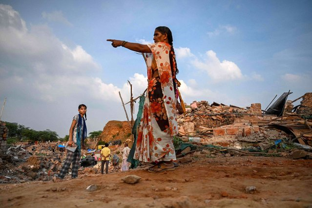 A woman points towards the debris of houses after local authorities razed a settlement that was said to be in a forest land in Khori village at Faridabad district in the Indian state of Haryana on July 15, 2021. (Photo by Money Sharma/AFP Photo)