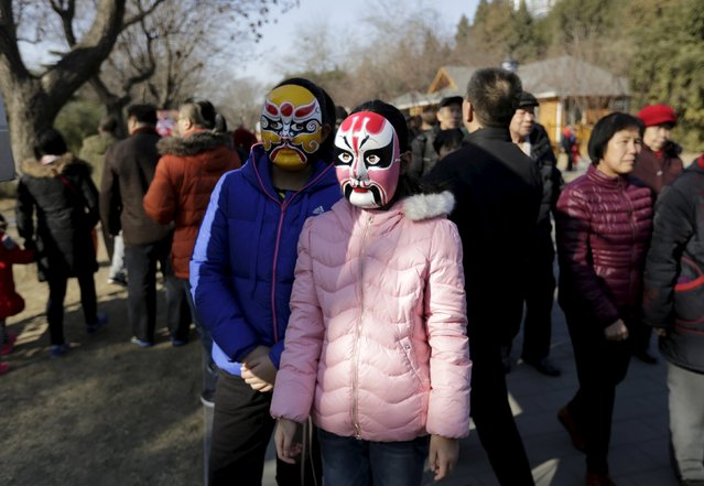 Two girls wearing Beijing Opera masks pose for a photo at a Spring Festival temple fair on the second day of the Chinese Lunar New Year of the Monkey in Beijing, China, February 9, 2016. (Photo by Jason Lee/Reuters)