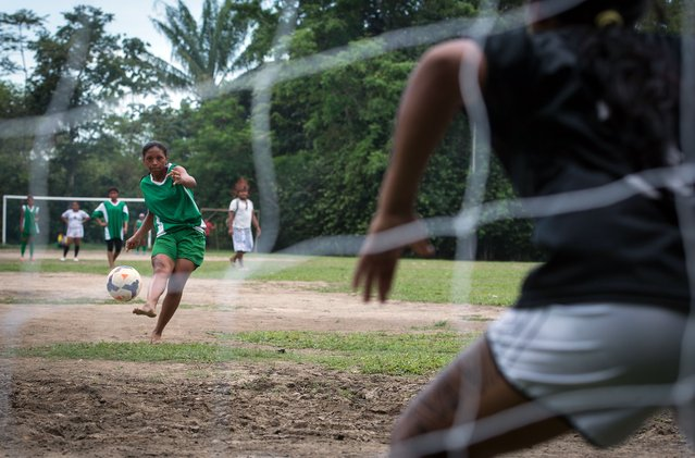 A member of the Satere Mawe tribe shoots at the goal during the final match of Peladao, the amateur football tournament, in Manaus, Amazonas state, Brazil, on November 24, 2013. (Photo by Yasuyoshi Chiba/AFP Photo)