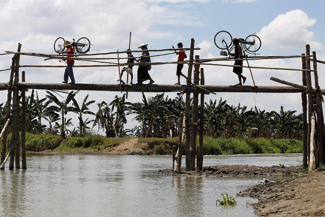Filipino evacuees cross a makeshift bridge in Mamasapano, Maguindanao Province, Southern Philippines, 31 March 2015. The Philippines' military announced a halt to a month-long military offensive against Muslim rebels that prompted the exodus of tens of thousands of people in southern Philippines. (Photo by Ritchie B. Tongo/EPA)
